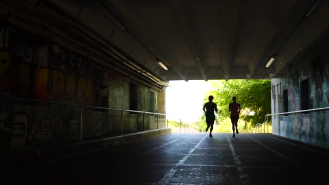 young couple jogging together - underpass stock videos and b-roll footage