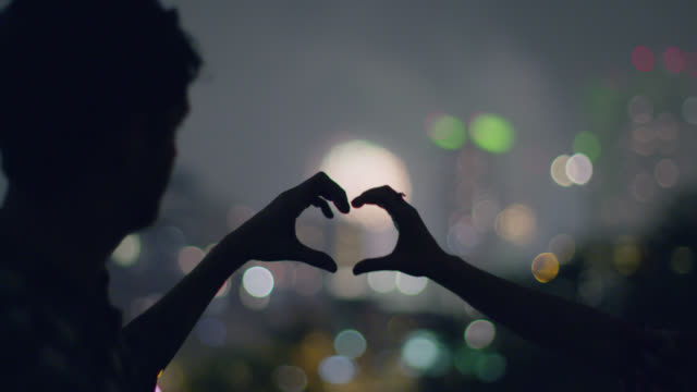 Young couple join hands to make a heart shape and frame the fireworks bursting in the distance