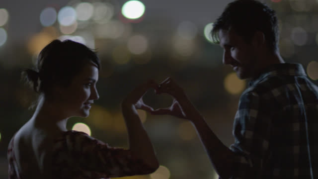 young couple join hands to make a heart - heart shape stock videos & royalty-free footage
