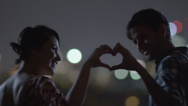 Young couple join hands to make a heart