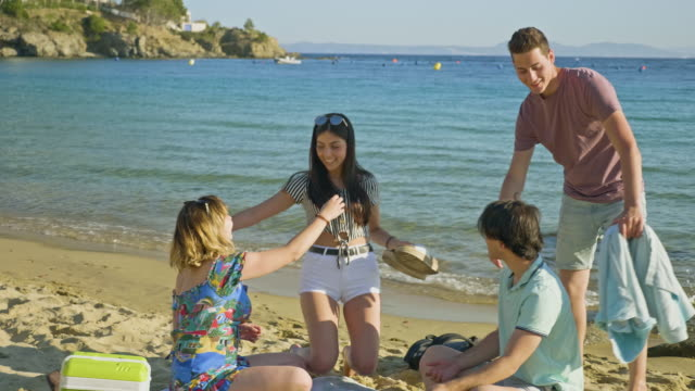 young couple joining friend at costa brava beach - asciugamano video stock e b–roll
