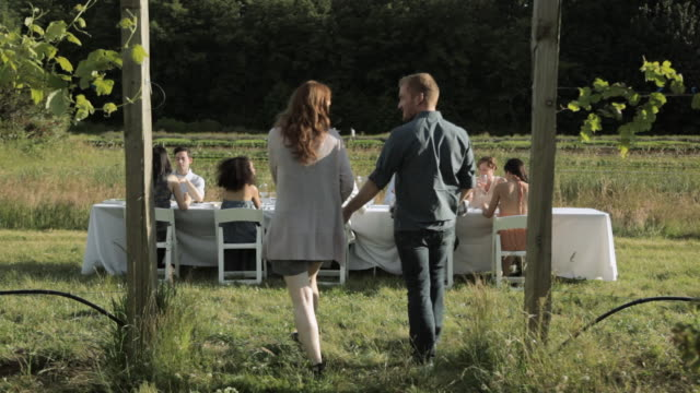 Young couple joining friends at farm dinner party