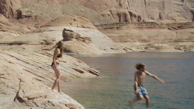 ws pan young couple jumping from rocky shore into lake powell / utah, usa - lake powell stock videos and b-roll footage