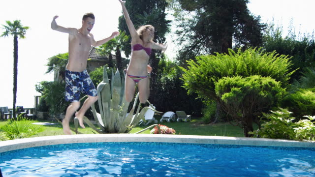young couple jumping into the pool - young couple stock videos & royalty-free footage