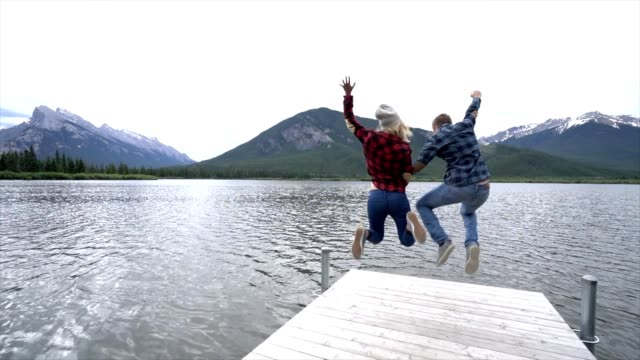 Young couple jumping mid-air by the mountain lake