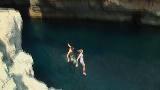 ws td zi young couple jumping off cliff to sea / mijet, croatia - klippe stock-videos und b-roll-filmmaterial
