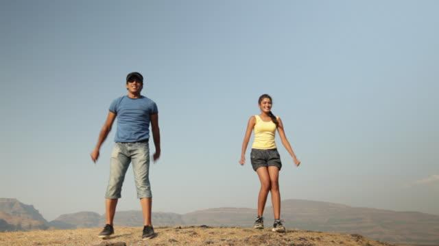vídeos de stock, filmes e b-roll de young couple jumping  - braço humano