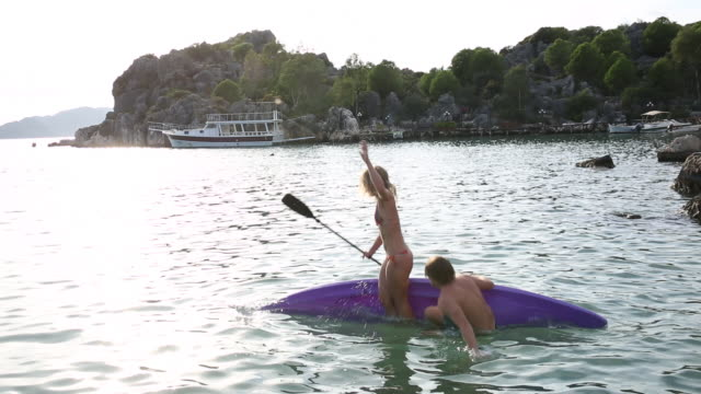 Young couple kayak into serene bay, playfully