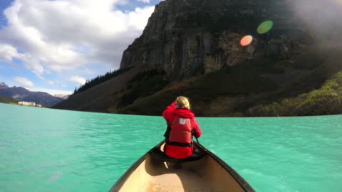 young couple kayaking on lake louise alberta canada - banff nationalpark stock-videos und b-roll-filmmaterial