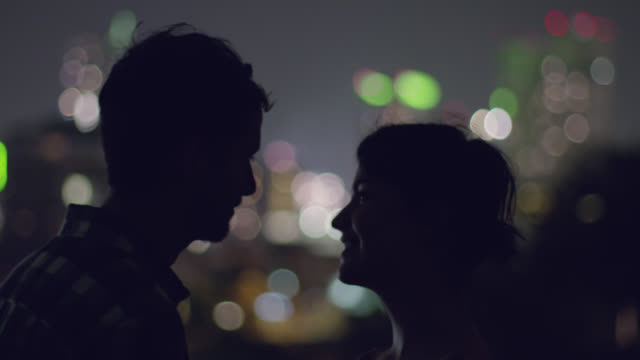 young couple kiss overlooking city skyline as fireworks burst in the distance - couple relationship stock videos & royalty-free footage