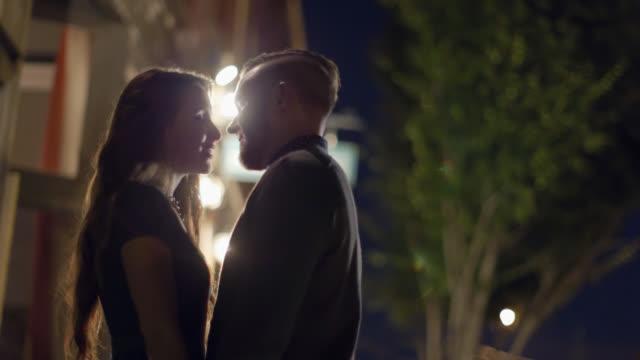 vidéos et rushes de young couple kisses outside of downtown restaurant at night - éclairage public
