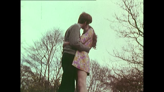 young couple kissing and walking in the woods in 1960's - bbc archive stock-videos und b-roll-filmmaterial