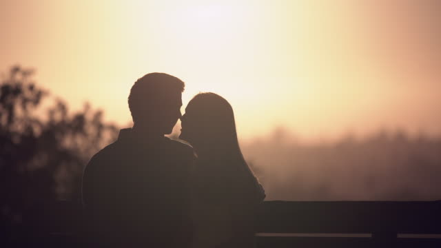 ms  young couple kissing at sunset - falling in love stock videos & royalty-free footage