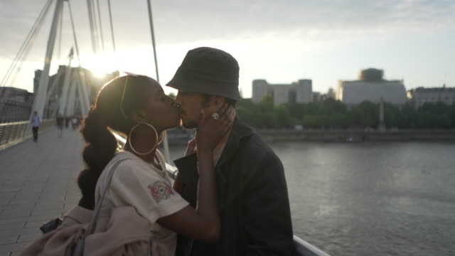 young couple kissing each other at sunset - kissing stock videos & royalty-free footage