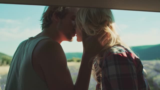 young couple kissing in van during vacation - falling in love stock videos and b-roll footage