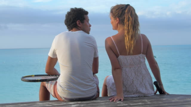 Young couple kissing on a dock overlooking the ocean after playing tennis.