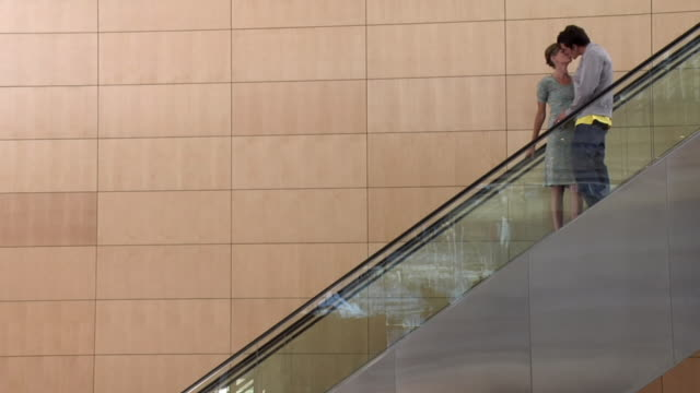 SLO MO WS Young couple kissing on escalator, Cape Town, South Africa