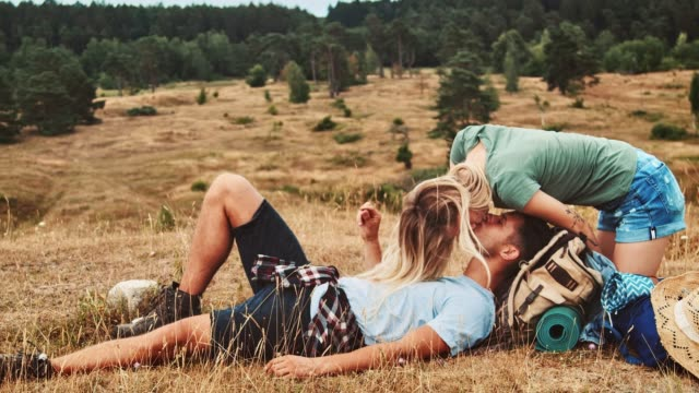 vídeos de stock e filmes b-roll de young couple kissing on field during vacation - amor