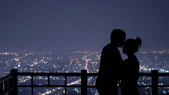 Young couple kissing on the background of the city at night , 4k(UHD)