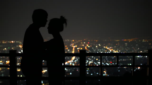 young couple kissing on the background of the city at night urban scene, 4k(uhd) - roof stock videos and b-roll footage