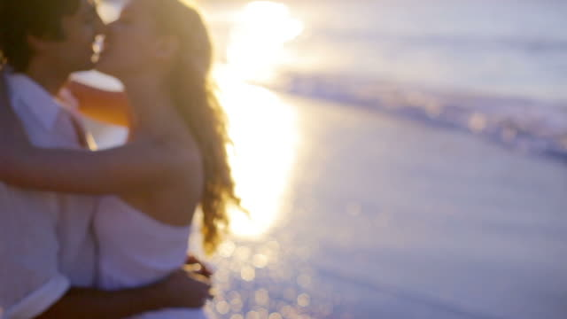 couple kissing on the beach during the sunset - dissolvenza in chiusura video stock e b–roll