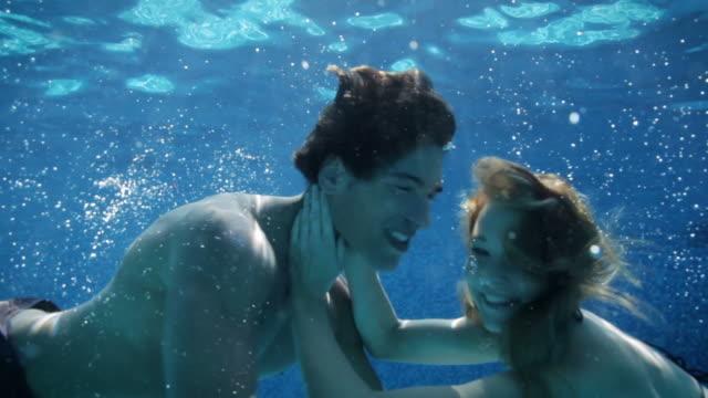 vídeos de stock e filmes b-roll de jovem casal a beijar debaixo de água na piscina - subaquático
