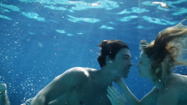 stockvideo's en b-roll-footage met young couple kissing under water in pool - halfgekleed