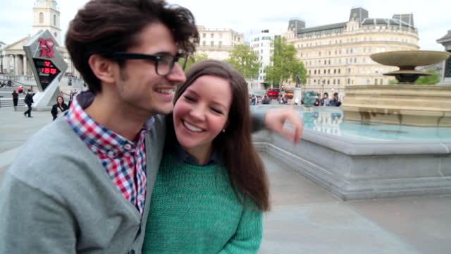 vidéos et rushes de young couple laugh and flirt as they walk through trafalgar square. - dimanche