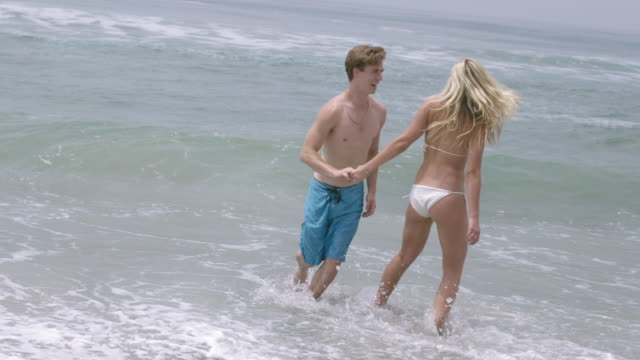 young couple laugh and run in slow motion by the pacific ocean hd - vesper stock stock videos & royalty-free footage