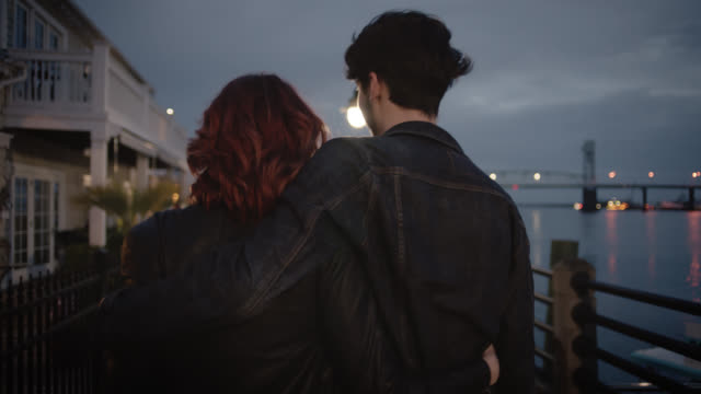 vídeos de stock e filmes b-roll de ms slo mo. young couple laugh and stroll down riverfront boardwalk with their arms around each other. - casaco de ganga