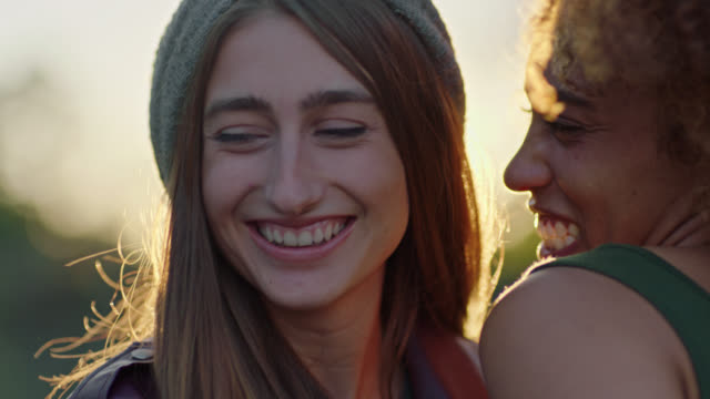 CU SLO MO. Young couple laugh together and gaze at each other as the sun sets.