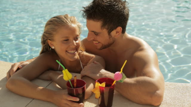 young couple laughing with drinks at side of pool - tropical drink stock videos & royalty-free footage