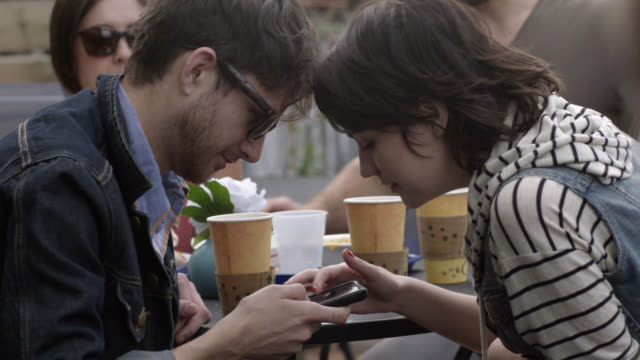 Young couple lean over smartphone at outdoor caf_