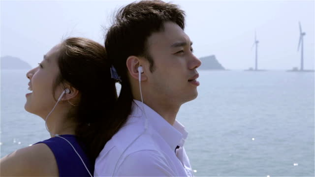 stockvideo's en b-roll-footage met young couple listening to music with ear bud at beach and they look at each other - in ear koptelefoon