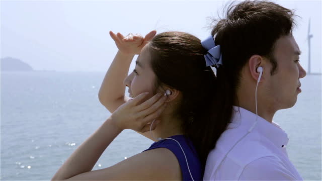 young couple listening to music with ear bud at beach and they look at each other - korea点の映像素材/bロール