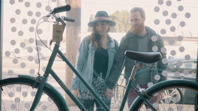 a young couple look at a bicycle through a store window - partire bildbanksvideor och videomaterial från bakom kulisserna