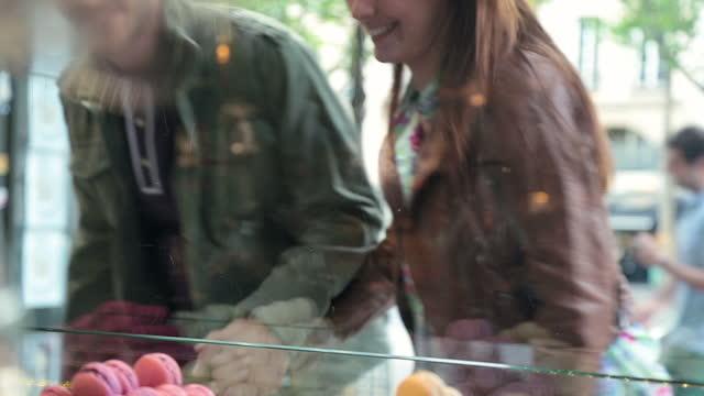 vídeos de stock e filmes b-roll de young couple look at colorful macaroons in the window of a french bakery and pick out the ones they want. - cultura francesa
