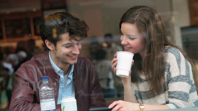 Young couple look at smartphone and chat over coffee in the window seat of a London cafe.
