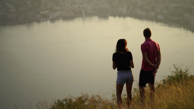 young couple look out at sunset and view of lake below - top capo di vestiario video stock e b–roll