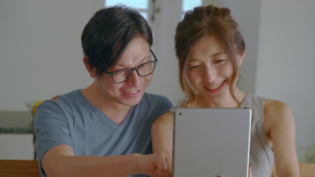 リビングルームでデジタルタブレットを見ている若いカップル - living room点の映像素材/bロール