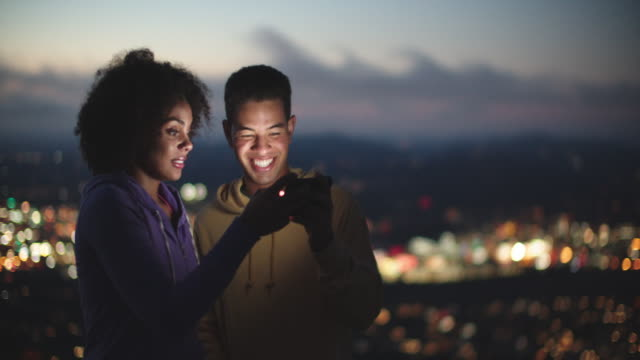 young couple looking at a phone at night - afro hairstyle stock videos & royalty-free footage