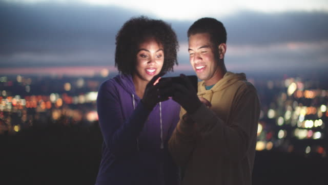 young couple looking at a phone at night - high up stock videos & royalty-free footage