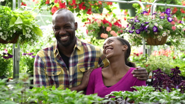 young couple looking at camera while standing in a greenhouse - whidbey island shop stock videos and b-roll footage