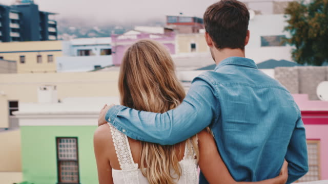 young couple looking at cityscape from rooftop - coppia di giovani video stock e b–roll