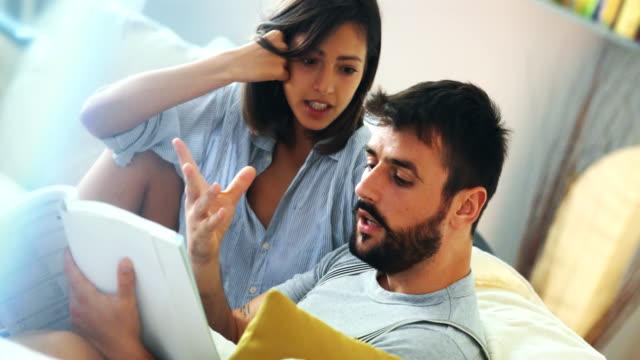vídeos y material grabado en eventos de stock de joven pareja mirando catálogos de decoración. - incertidumbre