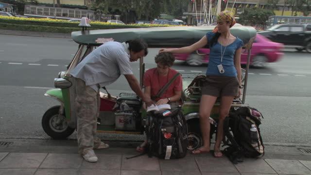 WS ZI Young couple looking at guidebook and talking to taxi bike driver, Bangkok, Thailand