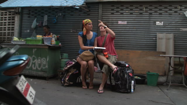 ws zi ms young couple looking at guidebook in city backstreet, bangkok, thailand - zaino da montagna video stock e b–roll