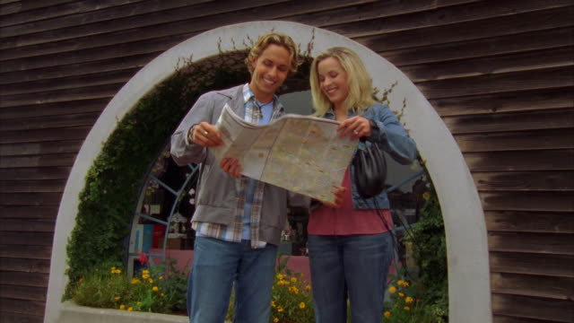 ms, young couple looking at map in front of gift shop, morro bay, california, usa - upside down stock videos & royalty-free footage
