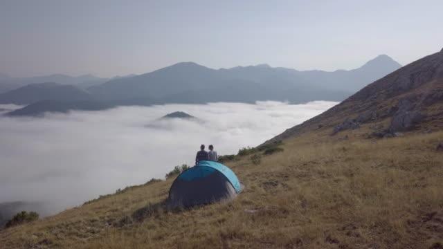 vídeos y material grabado en eventos de stock de young couple looking at the landscape over a mountain - tienda de campaña