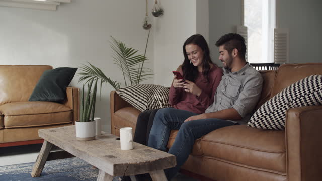 young couple looking at their phone at home - sitting stock videos & royalty-free footage